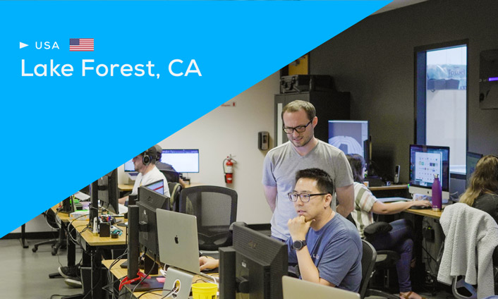 View the development team reviewing work with blue wedge overlaying image, text reads USA, Lake Forest, CA